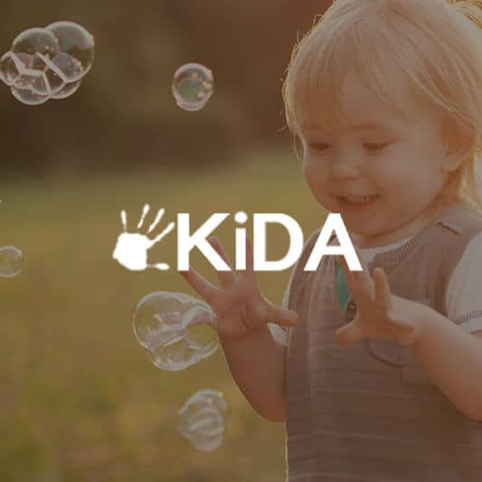 Little child smiling and playing with bubbles background image with KiDA logo in white