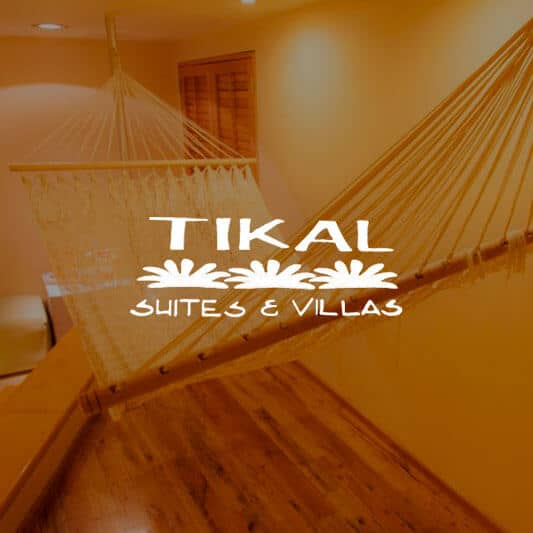 Luxury hanging hamaca in wooden motel room background image with Tikal Suites & Villas logo in white