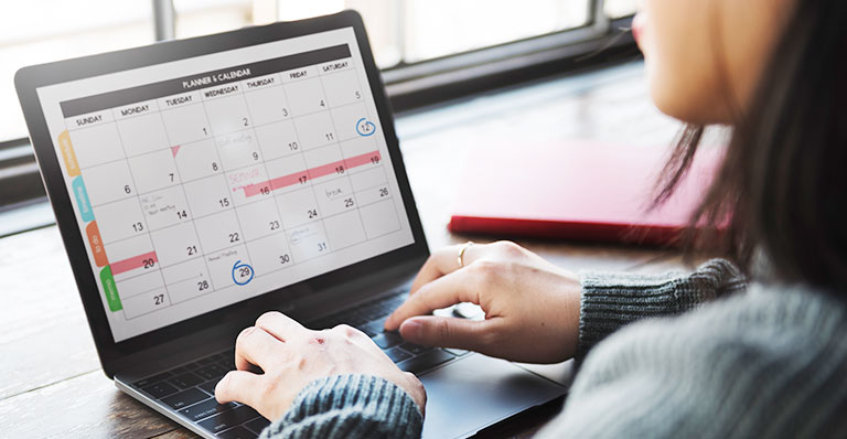 woman working on calencar laptop scheduling