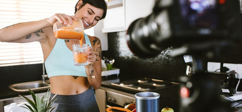 happy fitness woman recordin video making smoothie