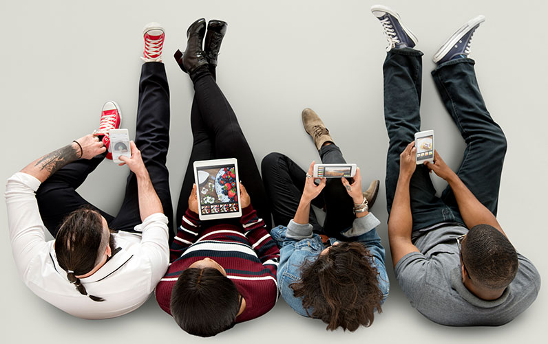four people sitting on the floor using devices