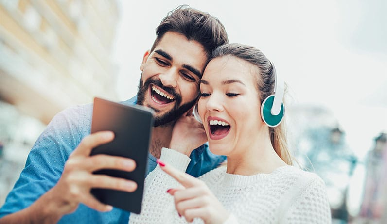 happy couple using tablet and headphones