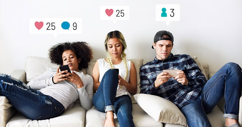 three young people sitting on the sofa and using social media on their phones