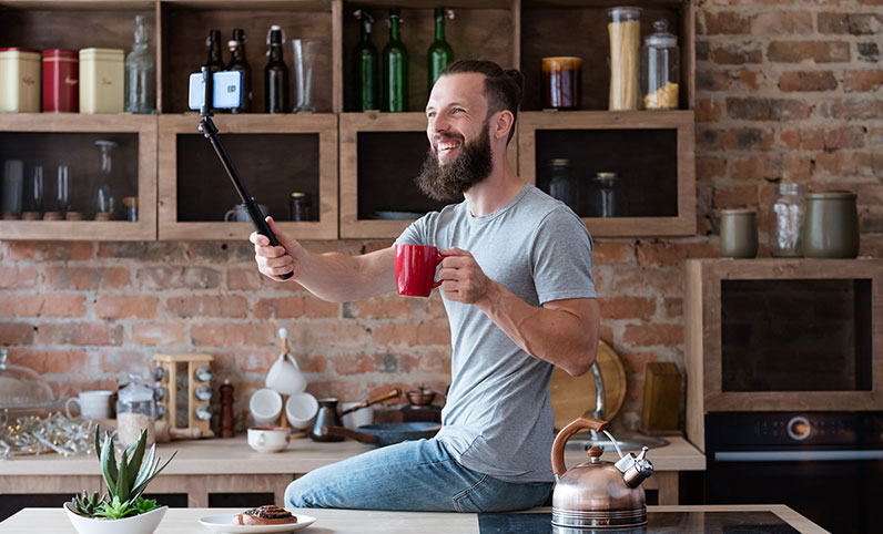 man holding a selfie stick looking at phone and holding cup
