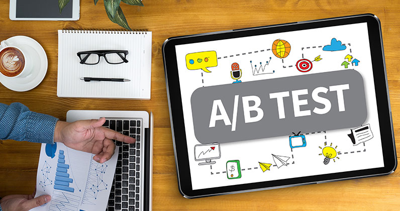 table with electronic devices big tablet showing ab test and mans hand