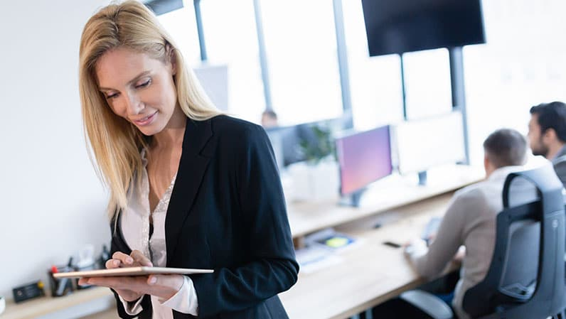 woman in office using a tablet and coworkers behind