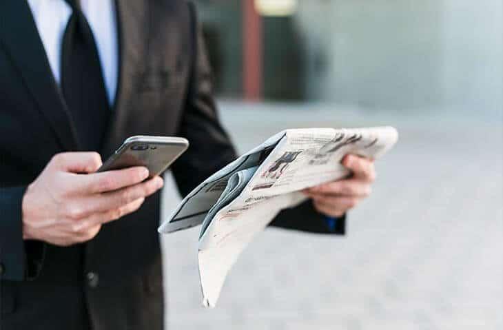hands holding phone newspaper