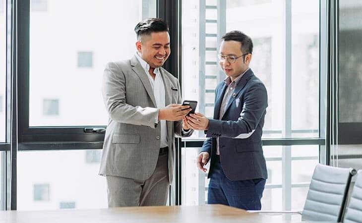 two men watching phone
