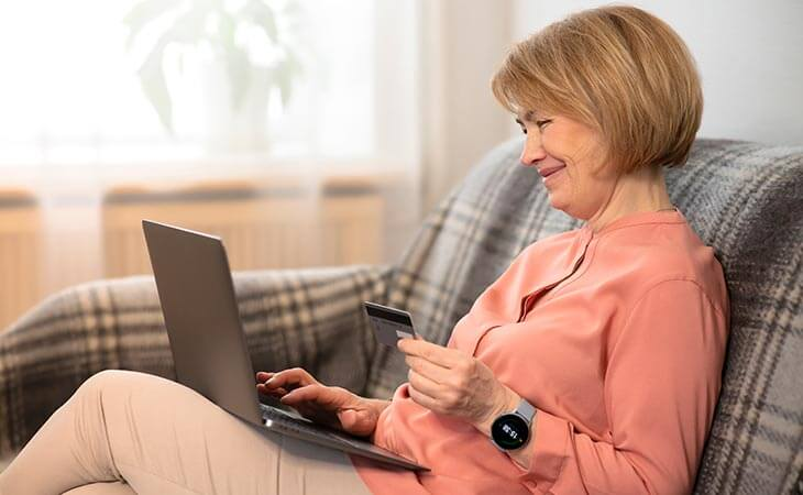 woman holding card laptop